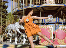 Cool real teenage girl with candy near carousels at amusement park walking, having fun Stock Photography