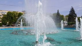 Cool refreshing fountain in the city. Water fountain in summer park. Landscape design. Light breeze, sunny day, dynamic scene, 4k video stock footage