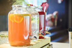 Cool refreshing fruit drinks. Poured into jars with a crane. Yellow, white, red Stock Photos