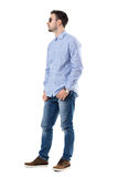 Cool relaxed smart casual young man wearing sunglasses with hands in pockets looking away. Royalty Free Stock Photos