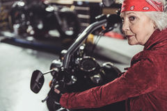 Cool retiree driving bike in mechanic shop Royalty Free Stock Photography