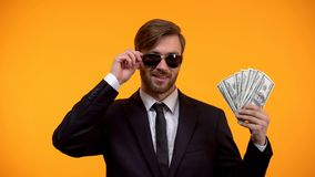 Cool rich man in sunglasses showing bunch of dollars, lottery winner, wellness. Stock photo stock photo
