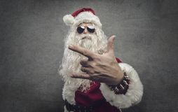 Cool rock Santa Claus. Cool Santa Claus making an heavy-metal gesture and staring at camera: rock Christmas concept royalty free stock photography