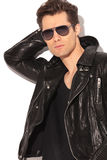 Cool rocker in leather jacket holding hand behind head. Portrait of a cool rocker in leather jacket holding hand behind head on white background Stock Photos