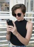 Cool 15 roczniaka nastoletniej dziewczyny patrzeje jej telefon komórkowego zdjęcia stock