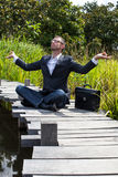 Cool 40s businessman practicing yoga on wooden path near water Stock Photos