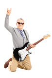 Cool senior man with an electric guitar giving a hand sign Stock Images