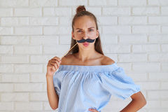 Cool serious girl holding fun paper mustache holding hand on a h Stock Photos