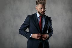 Cool young businessman buttoning his suit and looks down. In studio stock photo