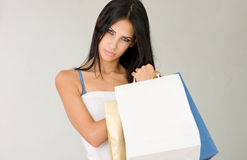 Cool shopper. Sensual young brunette woman holding colorful shopping bags stock image