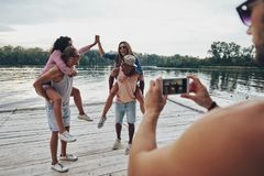 Cool shot!. Beautiful young couples spending carefree time while standing on the pier stock photo