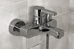 Cool shower faucet. Modern metallic faucet with water drops Royalty Free Stock Images