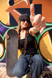 Cool skateboard woman. Next to a graffiti wall. The Graffiti is illegal art in a public park Royalty Free Stock Photography