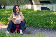 Skateboarder woman sitting on skateboard and drink coffee stock photos