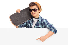 Cool skater boy pointing on a blank panel. Cool kid holding a skateboard and pointing on a blank panel with his hand isolated on white background royalty free stock photos