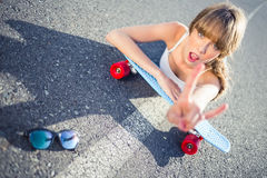 Cool skater girl doing rock and roll hand gesture Stock Photo