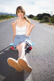 Cool skater girl doing sitting on her skateboard Royalty Free Stock Photos