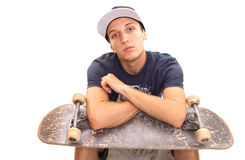 Cool skater sitting. Skater with cap sitting with a skate on his knees Royalty Free Stock Photos