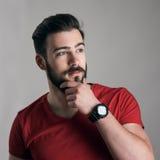 Cool som tänker den unga mannen med handen på hakan som trycker på hans skägg som bort ser fotografering för bildbyråer