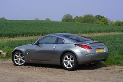 Cool sports car. Modern sports car next to field of crops, under blue sky stock image