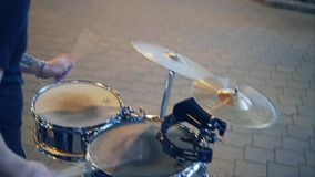 Cool street drummer playing on the streets of the evening city on the drums. Very cheerful musician. stock video