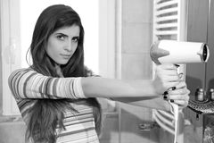 Cool strong woman pointing blow dryer like gun looking camera black and white Royalty Free Stock Photo