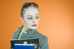 Cool student. Cool looking blond student with black sunglasses, holding a book and a magazine, with a confident attitude Stock Image