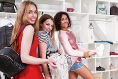 Cool stylish girls having fun standing in funny pose expressing true positive emotions in trendy clothing shop with. Racks of accessories and clothes in Stock Photo
