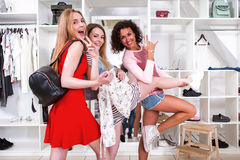 Cool stylish girls having fun standing in funny pose expressing true positive emotions in trendy clothing shop with. Racks of accessories and clothes in Royalty Free Stock Image