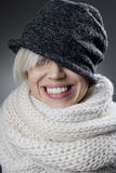 Cool stylish winter woman portrait. Attractive blonde eyes hidden under a hat smiling charmingly in volumetric white scarf. Warms clothes. cold season Royalty Free Stock Photo
