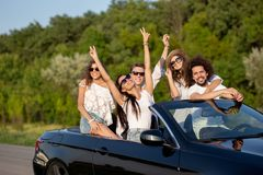 Cool stylish young dark-haired girls and guys in sunglasses smile in a black cabriolet on the road holding their hands royalty free stock image