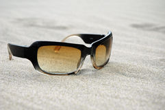Cool Sunglasses on a sandy beach. A pair of cool looking sunglasses on a sandy beach background royalty free stock photos