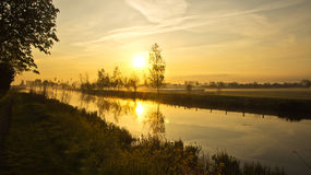 Cool sunrise above Dutch paddock. Sunrise above a Dutch paddock with view over a canal and distant farms on a cool morning Stock Photography