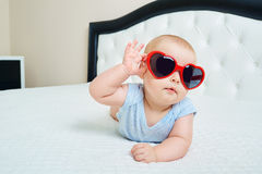 Cool super child.  Funny baby boy in solar glasses of red heart Royalty Free Stock Photos