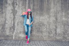 Cool swag culture. Young attractive hipster girl stands with pin. K skate board on concrete wall`s background, in denim jeans outfit, pink hat and shoes, holds a Royalty Free Stock Photo