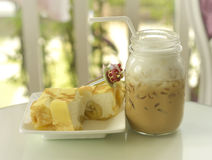 Cool sweet Banana Crepe Cake with ice coffee in glass bottle Royalty Free Stock Images