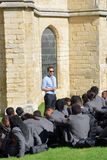 Cool teacher giving lecture in grounds of Cathedral Stock Images