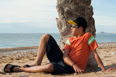 Cool teen. Cool looking teenager relaxing on a sandy beach Royalty Free Stock Photography