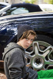 Cool teenage boy sitting in front of a rim of wheel Stock Images