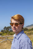 Cool teenage boy with sunglasses walks happy on the meadow Royalty Free Stock Image