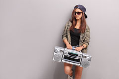 Cool teenage girl in hip hop outfit holding a radio. Cool teenage girl in hip hop outfit holding a ghetto blaster and leaning against a gray wall Royalty Free Stock Photography