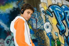 Cool teenager listening music. Portrait of a cool teenager listening music against a graffiti background Stock Images