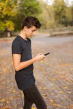 Cool teenager with a mobile on the street Stock Photography