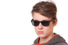 Cool teenager. Portrait of a cool teenage boy wearing sunglasses on white background Royalty Free Stock Image