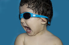 Cool toddler wearing sunglasses. Portrait of a cute little toddler girl wearing sunglasses. Mouth wide open and looking away. Isolated Royalty Free Stock Photography