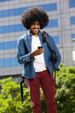 Cool travel guy walking with mobile phone Stock Photo