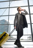 Cool travel man walking with mobile phone and suitcase Stock Images