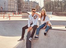 Cool trendy students are sitting at sunny skatepark with their longboards stock photos