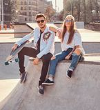 Cool trendy students are sitting at sunny skatepark with their longboards royalty free stock images