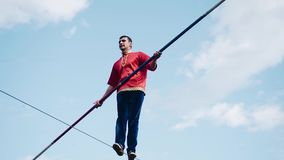 Cool tricks with a pole above the ground. A man walking on a rope stock video footage